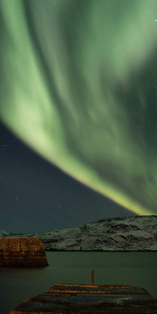 green northern light behind mountain on pontoon