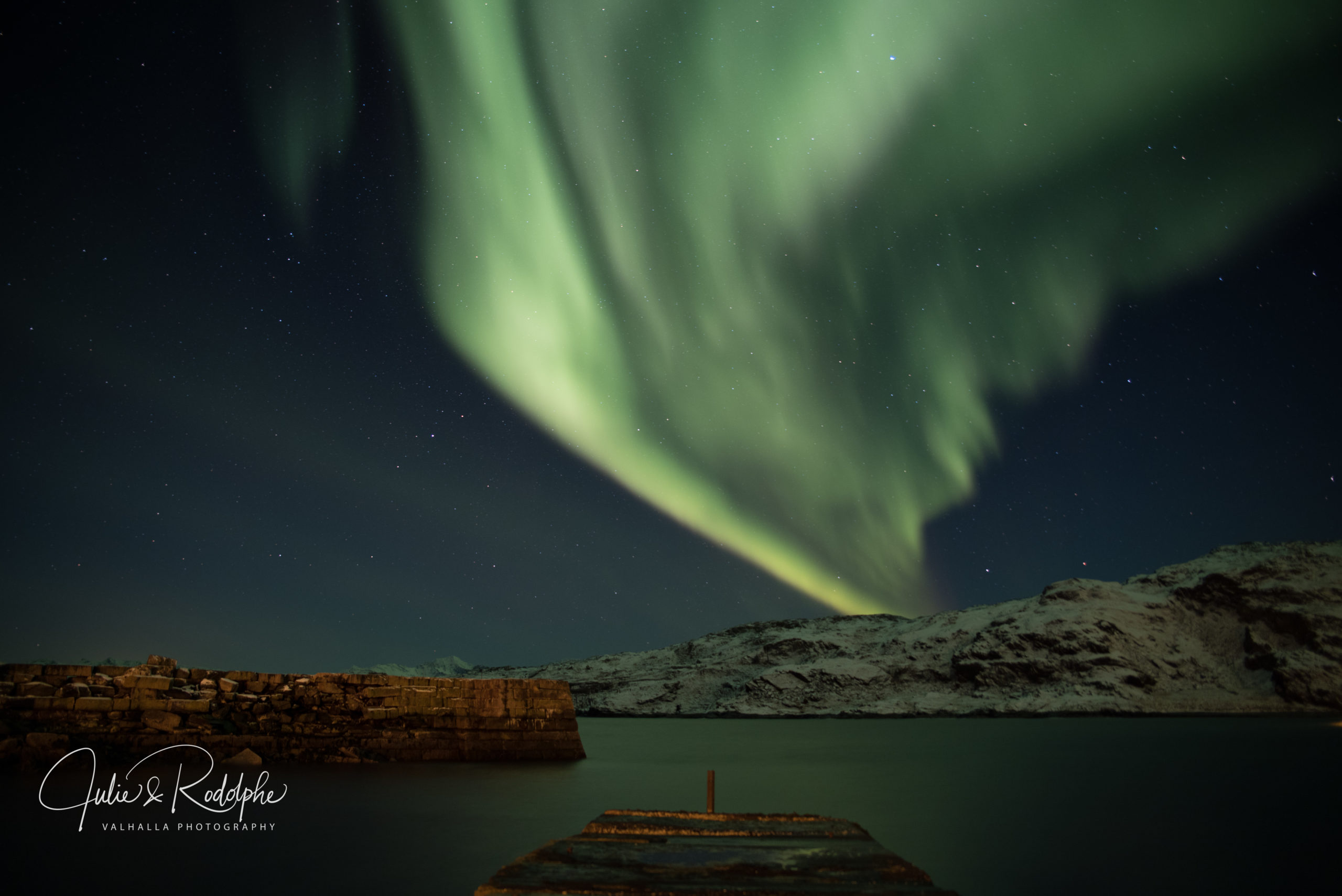 green northern light behind mountain on pontoon